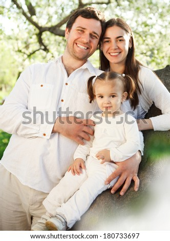 Happy young family with baby girl outdoors. Spring