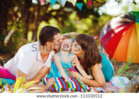 Happy young family with child resting outdoors in summer park