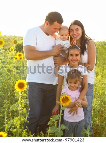 Happy young family with children in sunflowers field