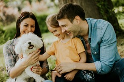 Happy young family with cute bichon dog in the park