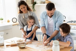 Happy young family with cute little preschooler kids have fun making dough baking pie or pastry in modern kitchen together, overjoyed parents teach small children doing bakery cooking at home