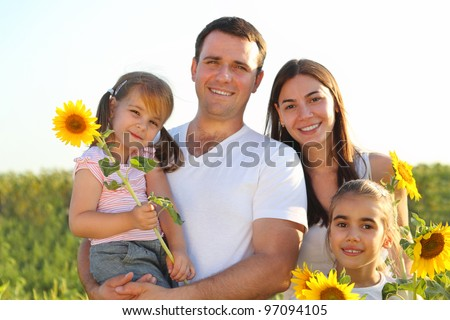 Happy young family with daughters holding sunflowers