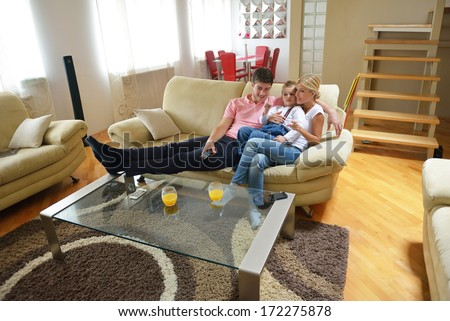 happy young family with kids in bright modern living room have fun and looking big flat lcd tv