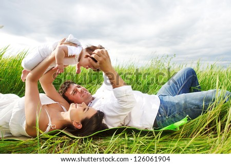Happy young family with little baby girl outdoors