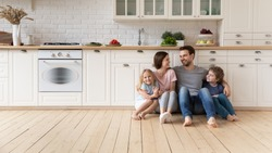 Happy young family with little children sit on warm wooden floor in new modern design kitchen, overjoyed parents with excited small kids relax rest in own renovated apartment, moving concept