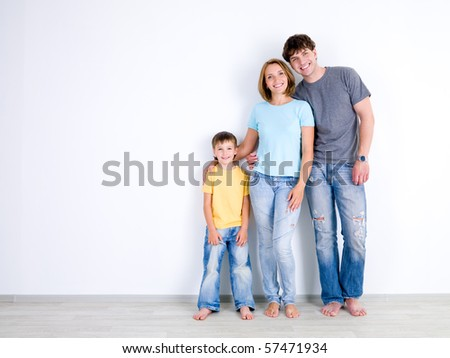 Happy young family with little son standing together in casuals near the empty wall - indoors