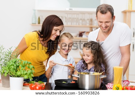 Shutterstock Happy young family with Mum, Dad and two young children cooking in the kitchen preparing a spaghetti meal together