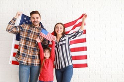 Happy young family with national flags of USA near white brick wall