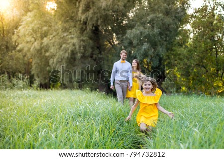 Happy young family with one child having fun together. concept - father, mother and child daughter having fun and playing in nature. yellow clothes. summer sunny day. in green nature together rest