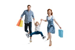 Happy young family with one child holding shopping bags and smiling at camera isolated on white