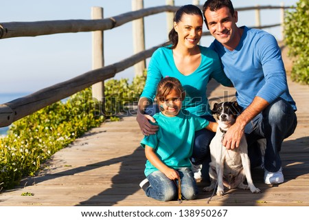 happy young family with pet dog at the beach