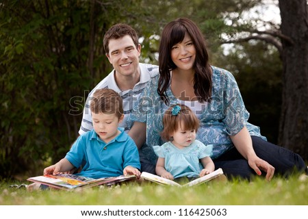 Happy young family with pregnant mother sitting and reading in park - stock photo