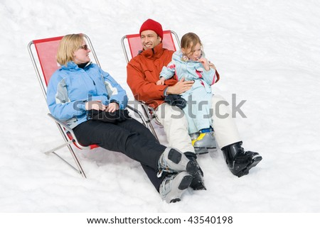 Happy young family with ski boots sitting in chairs