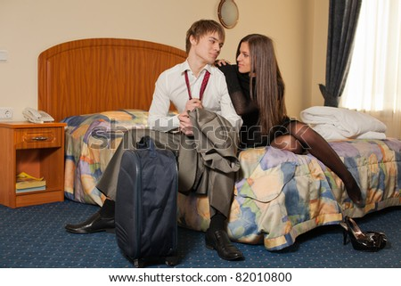 Happy young family with suitcases sits in the bed. Vacation. - stock photo