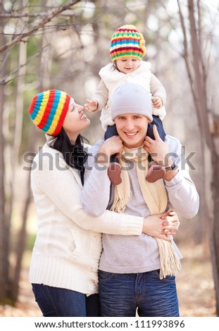 happy young family with their daughter spending time outdoor in the autumn park