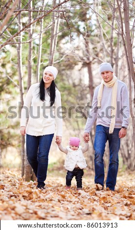 happy young family with their daughter spending time outdoor in the autumn park (focus on the man and woman)