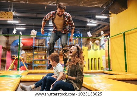 Happy young family with their little son jumping on a trampoline together at the entertainment centre