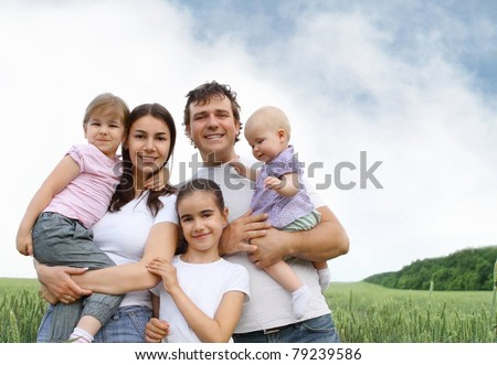 Happy young family with three daughters outdoors