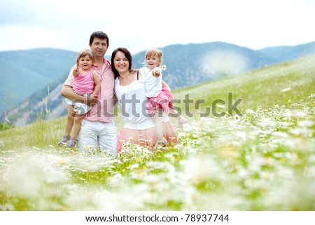 Happy young family with twins resting outdoors