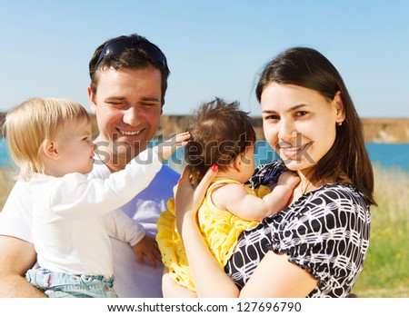 Happy young family with two children near the lake outdoors