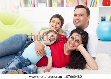 Happy young family with two small kids together at home