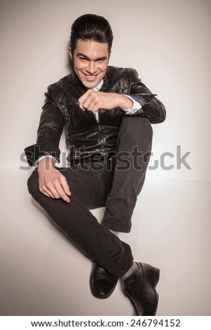 Happy young fashion man relaxing on white studio background, holding his hands on his kness while lookig at the camera.