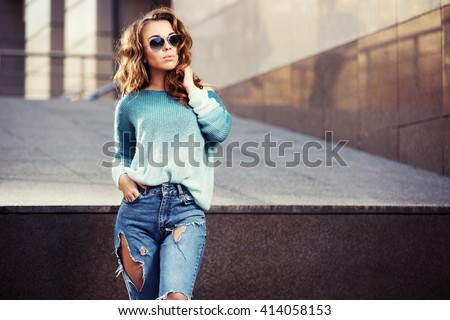 Happy young fashion woman in sunglasses walking in city street Female stylish model in ripped jeans outdoor