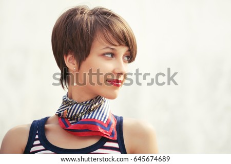 Happy young fashion woman walking outdoor Stylish female model in tank top and silk scarf