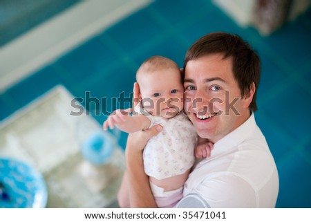 Happy young father and his baby daughter at home