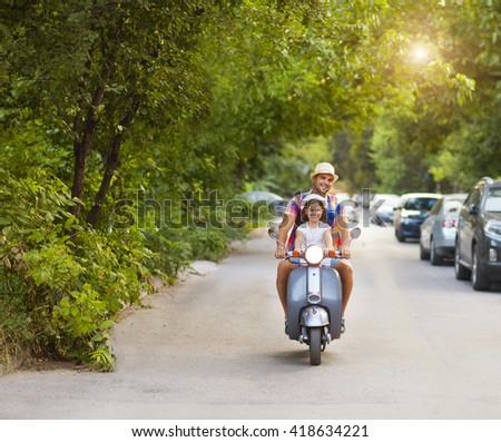 Happy young father and little daughter riding a vintage scooter in the street wearing hats. Holiday and travel concept