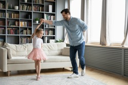 Happy young father dance with cute little daughter princess wearing crown and beautiful skirt, smiling dad have fun engaged in funny activity playing with small preschooler girl child at home