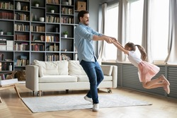 Happy young father have fun with little preschooler daughter relax together at home, overjoyed dad dance and swirl sway with excited small girl child, enjoy family weekend in living room