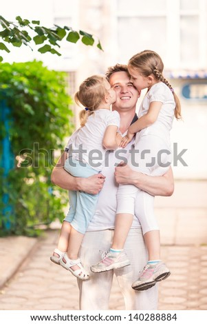 Happy young father holding his kids on hands outdoor