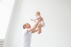 Happy young father lifting cute baby up high in air, spending and enjoying time together with daughter