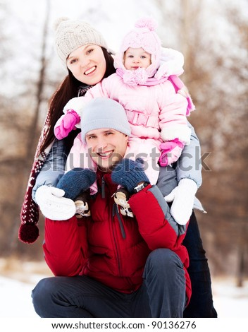 happy young father, mother and their daughter spending time outdoor in the winter park (focus on the man)