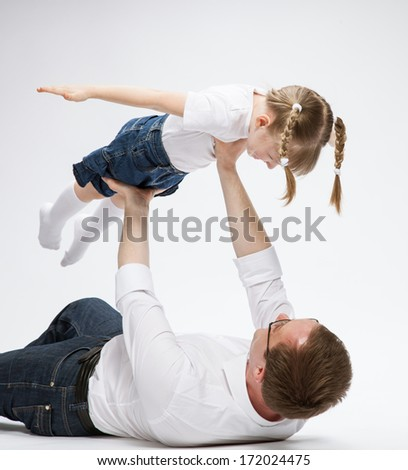 Happy young father playing with his smiling daughter neutral background