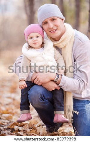 happy young father with his daughter spending time outdoor in the autumn park