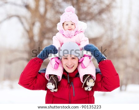 happy young father with his daughter spending time outdoor in the winter park