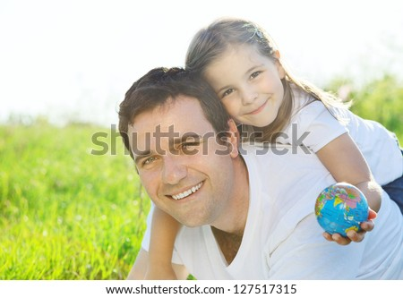 Happy young father with little daughter outdoors holding globe - stock photo