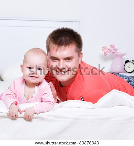 Happy young father with smiling baby lying on bed in bedroom - stock photo