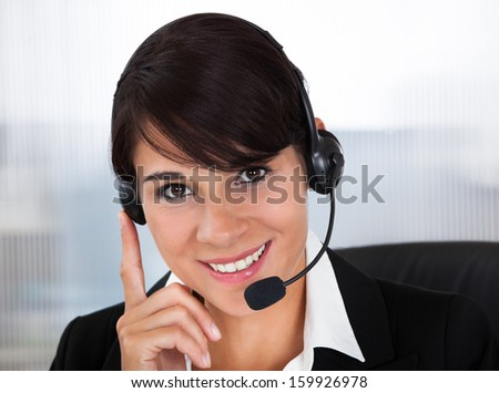 Happy Young Female Callcenter Employee Wearing Headset In Office