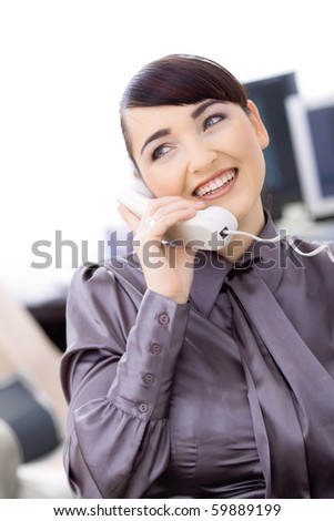 Happy young female customer service operator talking on landline phone, sitting in front of computer screens, smiling. - stock photo