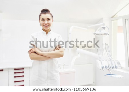 Happy young female dentist with tools over medical office background. Stomatology and healthcare concept.
