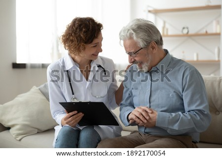 Happy young female doctor nurse laughing, sharing good health test news with happy older senior man in eyeglasses, visiting retired patient at home, medical insurance, domestic geriatric help concept.