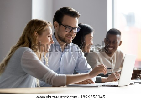 Happy young female employee discussing online project, showing computer presentation to skilled team leader in eyeglasses. Friendly diverse colleagues working in pairs on laptop, using applications.