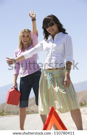 Happy young female friends hitchhiking