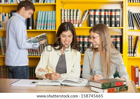 Happy young female friends studying together at table in university library