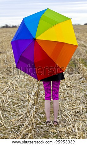Happy young female  holding an rainbow colored umbrella