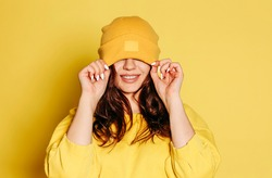 Happy young female in trendy yellow sweatshirt and knitted hat covering eyes smiling brightly against yellow background
