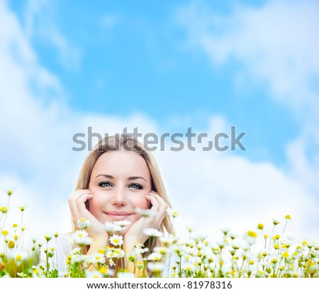 Happy young female lying on the flower field, over blue cloudy sky, with copyspace, leisure, fun and wellness concept - stock photo